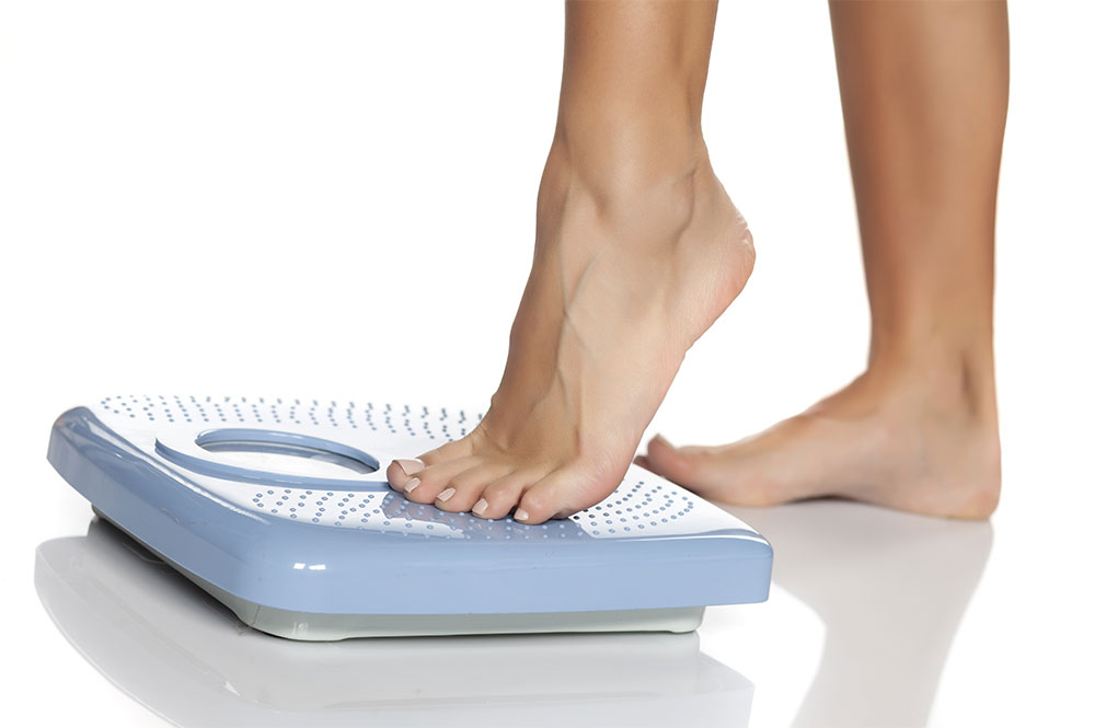 Image of person stepping on weighing scales